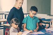 Positive female school teacher watching kids doing their task