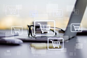 Online shopping concept with digital supermarket cart in squares on blurry laptop background.