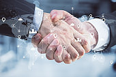 Handshake with global glowing connections on digital map.