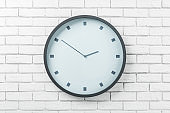 White round wall clock in black frame on light brick wall
