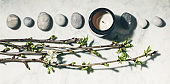 Flat lay composition with beautiful spring cherry branches, natural candle and grey stones on white marble background.