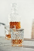 Glasses of whiskey with ice cubes and carafe close up