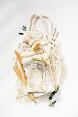 Zero waste, eco friendly concept. Glass jars, mesh bags, natural brush and bamboo cutlery on white background