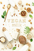 Non dairy plant based milk in bottles and ingredients on light background with wood letters. Alternative lactose free milk substitute, flat lay