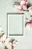 Photo frame mock up with space for text and beautiful spring magnolia flowers on grey stone background. Valentines day, mothers day, women's day, birthday concept