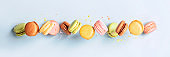 Vintage pastel colored French macaroons or macarons in motion falling on light blue background