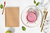 Composition with cutlery, measuring tape, blank paper notebook and alarm clock on color background. Diet concept, copy space
