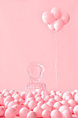 Empty transparent chair on pink pastel background among pink air balloons