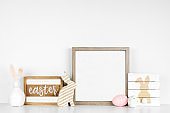 Mock up square wood frame with shabby chic Easter decor on a white shelf against a white wall
