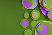 Abstract purple and green colored paper circles in green background.