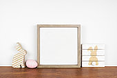 Mock up square wood frame with shabby chic Easter decor on a wood shelf against a white wall