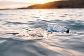 Garbage floating on sea or ocean water with plastic bottles and face masks. Sunset on background.