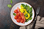 Salad with fresh baby spinach leaves, cherry tomatoes, sliced avocado and salty red salmon fish