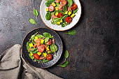 Salad with fresh baby spinach leaves, cherry tomatoes, sliced avocado and salty red salmon