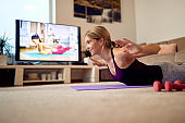 Happy sportswoman strengthening her back in Locust pose during home workout.