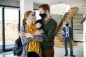 Happy couple with face masks embracing while buying new home during coronavirus pandemic.