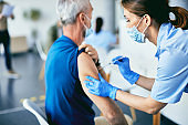 Female nurse giving COVID-19 vaccine to mature man at vaccination center,