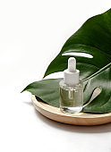Cosmetic bottle with green leaf on white background. Blank label for branding mock-up. Natural beauty product concept.