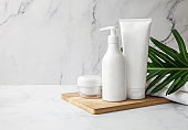 Natural cosmetics product set with green leaf on marble background. Blank label for branding mock-up. Natural beauty product concept. Copy space
