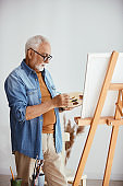 Senior artist painting on canvas at his home studio.