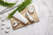 Natural cosmetic products set with green leaves on marble background. Natural beauty product concept. Flat lay, top view.