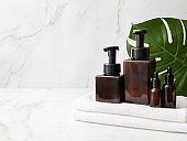 Amber glass cosmetic bottles set with towel and leaf on marble background. Blank label for branding mock-up. Natural beauty product concept. Copy space