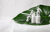 White cosmetic bottles and dropper with towel and monstera leaf on marble background. Blank label for branding mock-up. Natural beauty product concept.