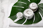 Cosmetic cream container jars with towel and leaf on marble background. Natural beauty product concept.