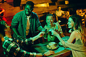 Multi-ethnic group of friends toasting with beer and having fun while gathering in a bar.