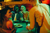 Group of young people having fun and laughing while waitress is serving them drinks in a pub.