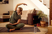 Happy athletic woman doing stretching exercises during home workout.