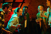 Multi-ethnic group of young people having fun during karaoke party in a bar.