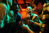 African American woman singing karaoke while spending the night out with her friends in a pub.
