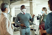 African American corporate manager talking while holding team meeting in the office during coronavirus pandemic.