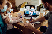 Close-up of family talking with doctor via video call over laptop during coronavirus pandemic.