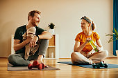 Happy couple sitting on the floor and talking while resting during home workout.