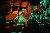Group of carefree friends singing having fun on night karaoke party in a bar.