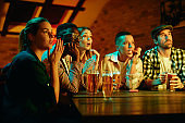 Multi-ethnic group of friends watching sports match with anticipation while drinking beer in a pub
