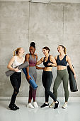 Group of diverse athletic women having fun while talking after exercise class at health club.