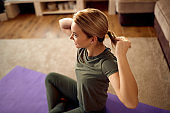 Happy athletic woman tying her hair in ponytail while getting ready for home workout.