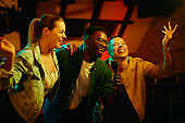 African American man and his female friends singing karaoke and having fun during their night out in a bar.