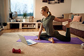 Side view of female athlete doing Yoga relaxation exercise in the living room.