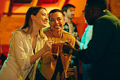 Young happy people toasting and celebrating their friendship during their night out in a pub.