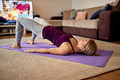 Athletic woman doing glute bridge exercise during home workout.