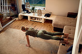 Above view of athletic woman practicing push-ups in the living room.