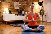 Zen-like woman in namaste pose meditating during home workout.