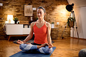 Zen-like athlete meditating with eyes closed while practicing Yoga at home.