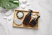 Amber glass cosmetic bottles with spa element and towel with leaf on marble background. Blank label for branding mock-up.