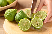 Hand holding kitchen knife and cutting bergamot fruit on wooden cutting board