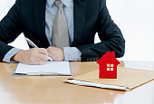 A House on document envelope with man signing purchase documents in background. while hand complete the insurance policy, rental documents and loan document. concept guy buying new house